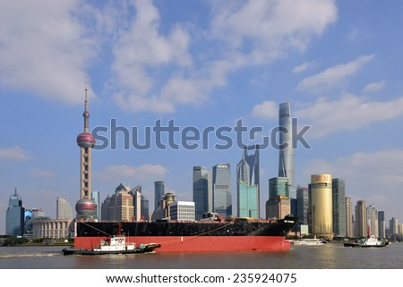 SHANGHAI, CHINA NOV 20. 2014: A huge ship is escorted through the Huangpu River of Shanghai, the world's busiest container port by  tugboats. In the background is he magnificent skyline of Shanghai. - stock photo