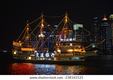 SHANGHAI, CHINA - NOV 19, 2014: A tour boat cruises the Huangpu River of Shanghai, these are a popular tourist attraction as the skyline is magnificent at night. - stock photo