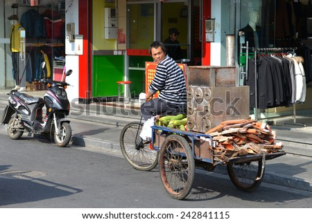 SHANGHAI, CHINA - NOVEMBER 10, 2014: An unidentified man rides a three-wheeled vehicle with a roaster which allows him to sell roasted corn in Qingpu District of Shanghai.  - stock photo