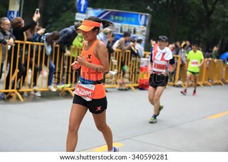 SHANGHAI,CHINA - NOVEMBER 08:Marathon runners running on city road at the 20th Shanghai Marathon NOVEMBER 08,2015 in Shanghai,China - stock photo