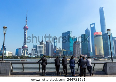 SHANGHAI, CHINA - OCT 24, 2014: A Group of Business People Looking at Shanghai Skyline. Shanghai is the largest Chinese city by population and the largest city proper by population in the world. - stock photo