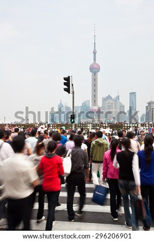 Shanghai, China - October 3, 2010: Commuters in a busy crosswalk at the Bund in Shanghai, China, with landmarks in the Pudong area in the background - stock photo