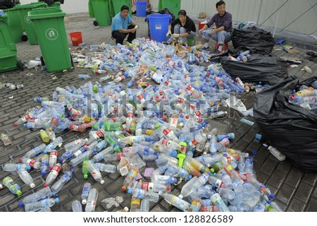 SHANGHAI, CHINA - OCTOBER 17: World Expo 2010, Chinese workers manually sort and recycle plastic bottles collected from exhibition visitors. October 17, 2010. - stock photo