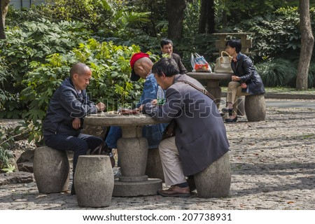 SHANGHAI, CHINA - 28th MARCH 2014: peoples square where people meet to talk and play board games in the park every morning