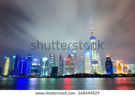 Shanghai city skyline at night over Huangpu river - stock photo