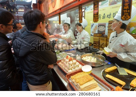 SHANGHAI, CN - MAR 17 2015:Chines lines up to buy Dim sum dumplings food at Yuyuan Tourist Mart in Shanghai, China.Dim sum dumplings it's the most popular and famous food in Shanghai, China - stock photo
