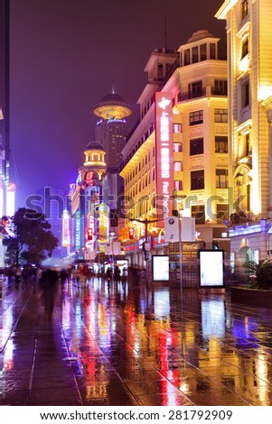 SHANGHAI, CN - OCT 31, 2014: Architecture of Nanjing Road - the main shopping street of Shanghai, China at night after rain with crowds of shopgoers - stock photo