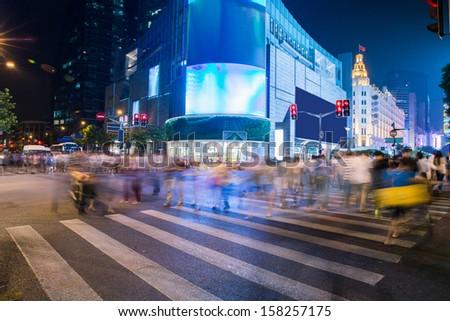 shanghai crossing at night. Night Shopping. Long exposure, blurred crowd. - stock photo
