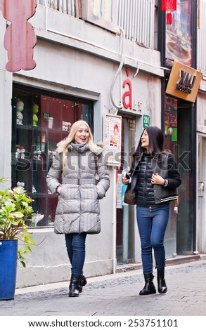 SHANGHAI-DEC. 4, 2014. Pretty girls at Tianzefang art area. Known for its small craft stores, coffee shops, trendy art studios and narrow alleys it became a popular tourist destination in Shanghai.  - stock photo