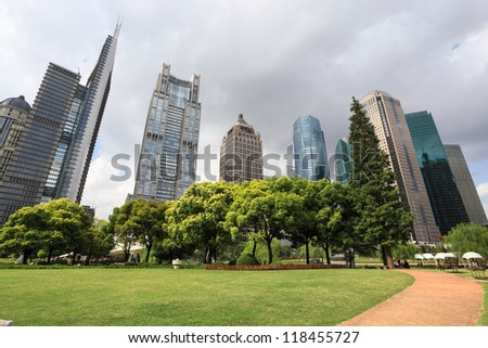 shanghai greenbelt park with modern building in cloudy