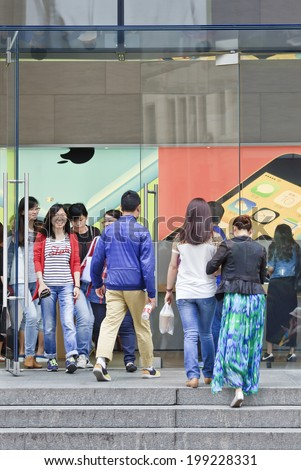 SHANGHAI-JUNE 4, 2014. People walk out the Shanghai Apple flag-store. According Umeng, China's largest analytic firm, 27% of China's smart-phones cost over  $500, and 80% of those are i Phones. - stock photo