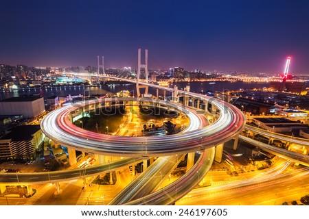 shanghai nanpu bridge at night ,  complex spiral approach bridge - stock photo
