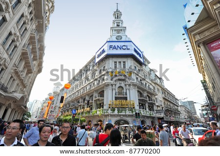 SHANGHAI - OCTOBER 4: tourist sites attract huge crowds of people during Chinese National Day holiday on October 4, 2011 in Shanghai, China. Here at Nanjing Lu commercial tourist street. - stock photo