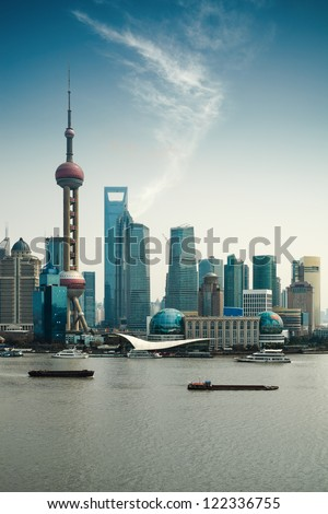 shanghai pudong against a blue sky with huangpu river - stock photo