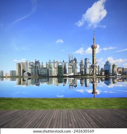 Shanghai's landmark skyline wood floor prospect and green lawn of green concept in city landscape architecture  - stock photo