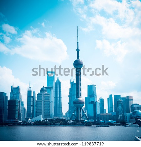 shanghai skyline against a blue sky - stock photo