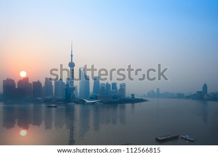 shanghai skyline and reflection in sunrise - stock photo