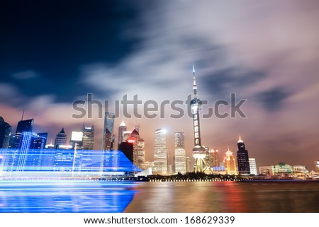 shanghai skyline at night with light trails of a cruise ship  - stock photo