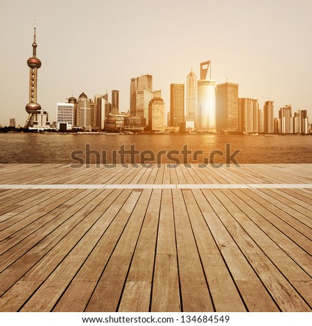 shanghai skyline in afternoon and reflection with wooden floor