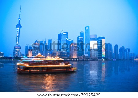 shanghai skyline with a cruise passing at dusk - stock photo