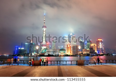 Shanghai urban city skyline over walkway at night - stock photo