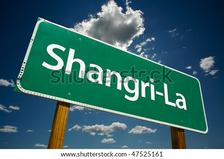 Shangri-La Green Road Sign with Dramatic Clouds and Sky. - stock photo