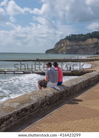 Shanklin Isle of Wight two people sitting on wall - stock photo