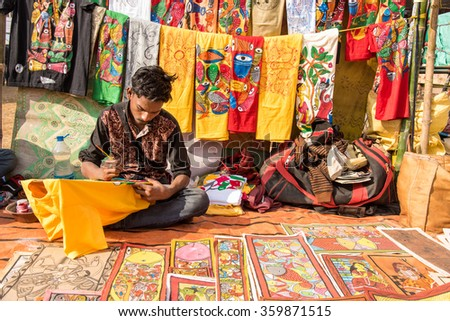 SHANTINIKETAN, INDIA - DECEMBER 26: An Indian artisan paints on colorful handicraft items for sale during the annual Poush Mela fair 2015 on December 26, 2015 in Shantiniketan, West Bengal, India. - stock photo