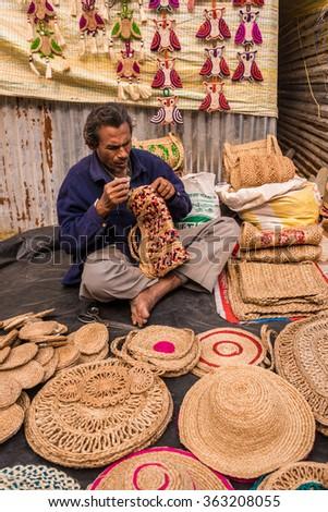 SHANTINIKETAN, INDIA - DECEMBER 25: An Indian artisan weaves creativel handicraft items for sale during the annual Poush Mela fair 2015 on December 25, 2015 in Shantiniketan, West Bengal, India. - stock photo
