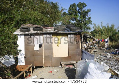 Shanty surrounded by trash in a rural area