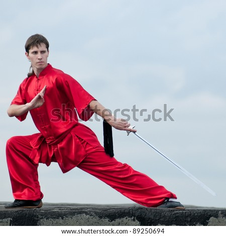Shaolin warriors wu shoo man in red with sword practice martial art outdoor. Kung fu - stock photo
