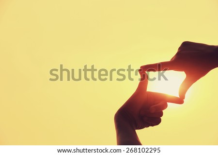shape making of hands against bright sea sunset and sunny golden way at water - stock photo