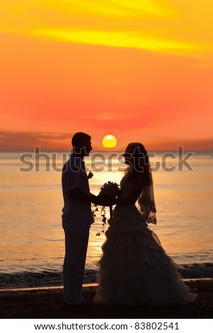 Shape of a bride and groom on the beach at sunrise time - stock photo