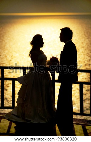 Shape of a bride and groom on the beach at sunset time - stock photo