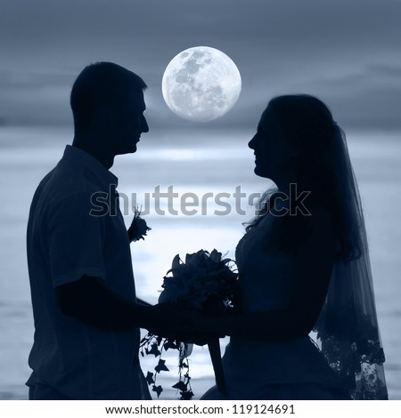 Shape of a bride and groom on the beach under the moon - stock photo