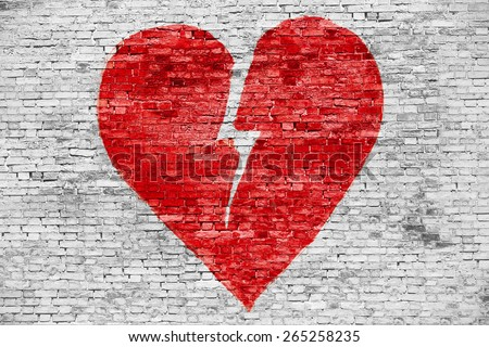 Shape of broken heart painted on white brick wall - stock photo