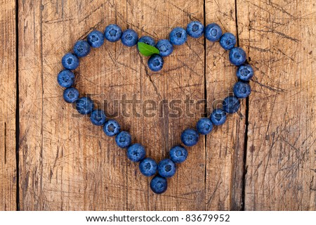 Shape of heart made of blueberries on wooden table - stock photo