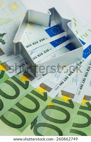Shape of house and euro banknotes - stock photo