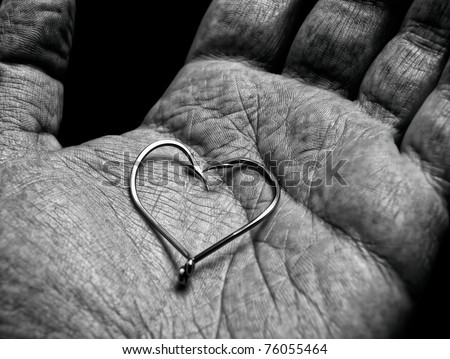 Shape or symbol of a heart in hand of an old fisherman... - stock photo