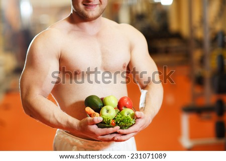 Shaped and healthy body man holding a fresh fruits, shaped abdominal - stock photo