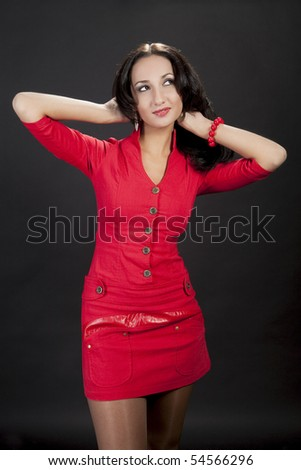 shaped and sexy looking young caucasian girl in red dress and skirt standing isolated over black background