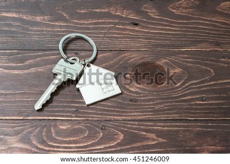 Shaped key ring resting on the wooden floor for the home or rental property. - stock photo