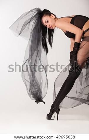 Shapely and hot young woman in all black erotic clothes - stock photo