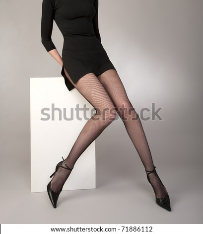 shapely girls  legs with black fishnet tights,  fashion shoes and  cocktail dress on a gray background studio shot - stock photo