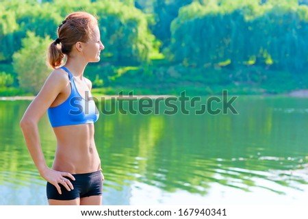 shapely, toned woman in sportswear rest on the nature - stock photo