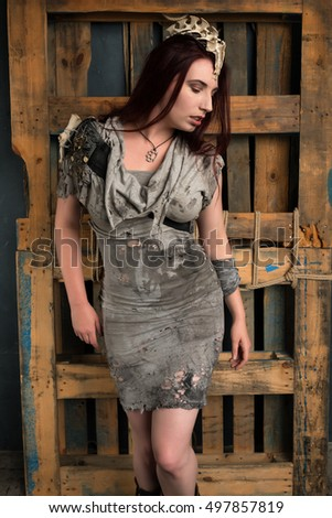 Shapely young brunette in a ragged gray dress