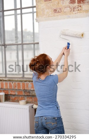 Shapely young woman doing DIY painting in her new home as she uses a roller to paint a white wall, back to the camera - stock photo