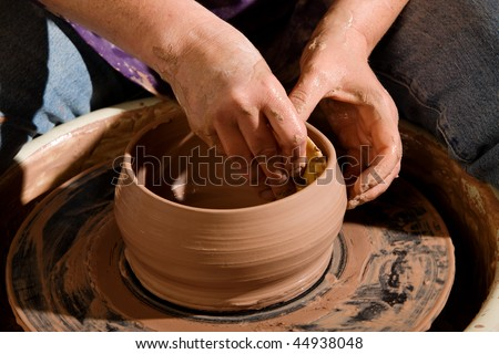 Shaping a new clay pot on a pottery wheel - stock photo