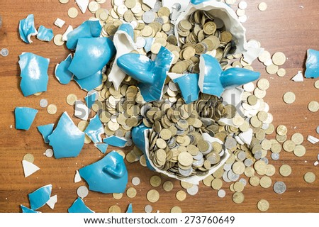 shards of blue ceramic piggy bank pig on a table after breaking full detail - stock photo
