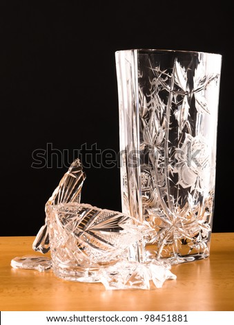 shards of broken vase lying next to another vase - stock photo